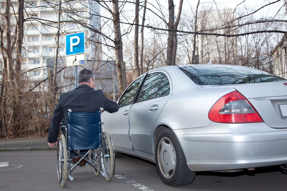 man on a wheelchair approaching his car