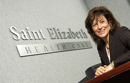 Shirlee Sharkey infront of wall with sign that reads Saint Elizabeth Health Care