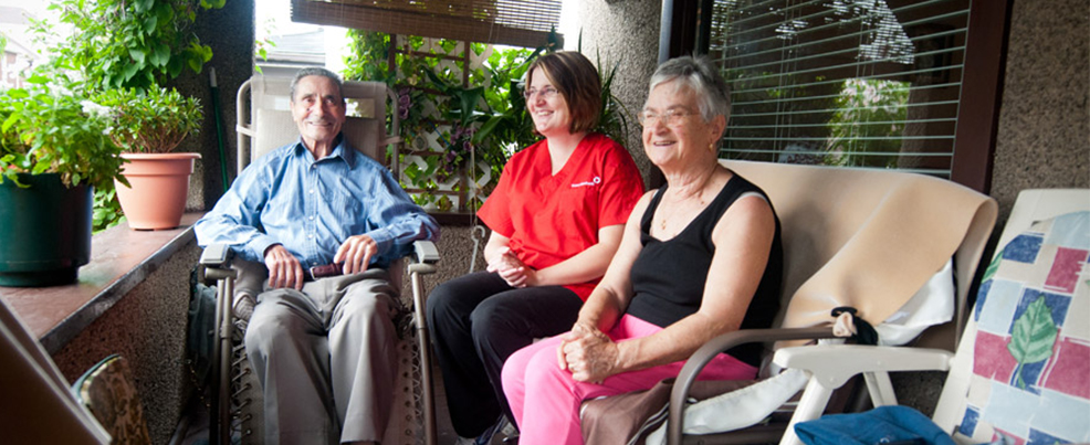 nurse with two elderly clients sitting on a porch